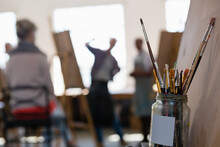 People Working At A Painting Class In An Art Studio, A Jar Of Paintbrushes In The Foreground