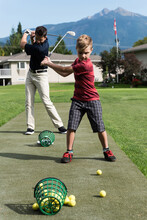 Caucasian Father And Son Hitting Some Practice Golf Balls Together In The Sun At Golf Club