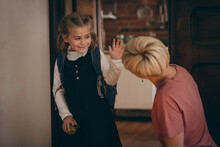 Caucasian Daughter Wearing Backpack Waving To Kneeling Mother Before Leaving Home For School