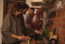 Diverse Group Of Smiling Friends Preparing Food In Kitchen Together