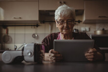Portrait Of Senior Woman Sitting In Kitchen, Using Tablet