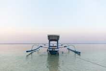 Small Fishing Boat Moored On Turquoise Seawater Under Cloudless Blue Sky In Peaceful Twilight