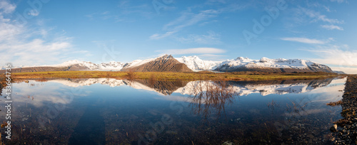 Fotografering Icelandic mountain range with beautiful snowcapped mountains reflected into still water