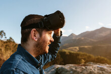 Curious Male Traveler Sitting On Hill And Experiencing Virtual Reality In Goggles In Mountains On Sunny Day