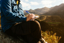 Side View Of Crop Unrecognizable Male Explorer Sitting On Hill In Mountains And Writing In Notepad During Vacation