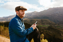 Side View Of Male Hiker Sitting On Hill And Browsing Smartphone While Admiring Mountainous Landscape