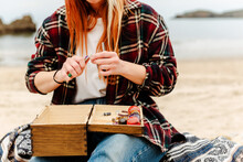Crop Anonymous Craftswoman Creating Handmade Bijouterie While Using Semiprecious Stones And Sitting On Beach Near Sea