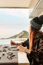 Side View Of Content Female Traveler Creating Handmade Accessories While Sitting At Wooden Table In Parked Truck At Seaside