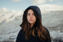 Young Gentle Female Traveler In Hood Looking At Camera Against Snowy Mountains In Winter On Sunny Day