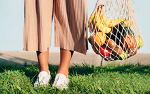 Unrecognizable Crop Female Standing In Nature With Cotton Mesh Bag With Ripe Fruits And Vegetables