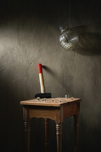 Hammer With Small Transparent Balls On Wooden Vintage Stool Under Hanging Vase On Rope On Gray Background