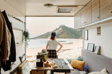 Back View Of Unrecognizable Traveling Female Artisan Standing Near Truck With Handmade Accessories On Background Of Sea And Mountains