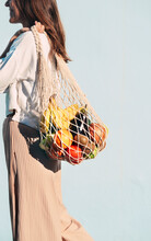Side View Of Cropped Smiling Female Standing With Assorted Fruits And Vegetables In Eco Friendly Mesh Bag Against Blue Wall In City And Looking Away