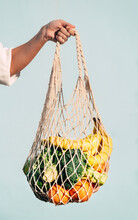 Cropped Unrecognizable Female Standing With Assorted Fruits And Vegetables In Eco Friendly Mesh Bag Against Blue Wall In City