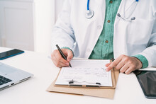 Cropped Unrecognizable Uniform With Stethoscope Taking Notes On Paper Sheet While Working In Clinic
