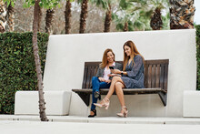 Content Best Female Friends With Cellphone Speaking While Sitting With Crossed Legs On Bench In Summer Town