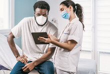 Young Female Doctor In Medical Uniform And Stethoscope Wearing Face Mask Speaking And Showing Result On Tablet To African American Man Patient During Appointment In Clinic