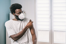 African American Man Patient Holding Cotton With Alcohol Disinfecting Arm After Covid Vaccine Procedure In Clinic During Coronavirus Outbreak