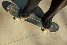 Close-up Of The Feet Of A Young Man Who Is Riding A Skateboard In The Street