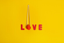 Top View Of Red Yarn Ball Between Food Sticks And Love Title On Yellow Background