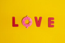 Top View Of Love Title With Red Letters And Pink Pompom Maker On Bright Background