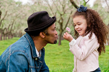 Side View Of Ethnic Father With Content Girl In Straw Hat Enjoying Blossoming Flower Aroma And Looking At Each Other In Park