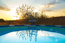 Round Swimming Pool With Warm Clean Water Placed On Spacious Verdant Nature At Bright Sunset