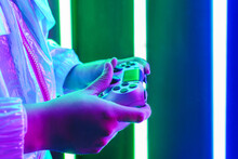 Side View Of Crop Unrecognizable Person With Gamepad Playing Video Game In Shiny Light
