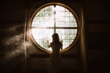 Back View Of Unrecognizable Gentle Female Touching Fence On Round Shaped Window In House In Sunlight