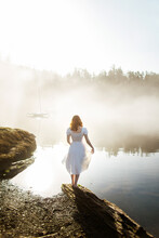 Back View Woman Standing Dressed In A White Dress On A Rock Looking At A Lake On A Foggy Day