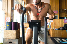 Crop Unrecognizable Male Athlete With Strong Naked Torso Exercising On Air Bike During Active Workout In Gym