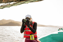 Cheerful Female Tourist With Digital Photo Camera Sitting On Boat Edge During Trip On Wavy Ocean