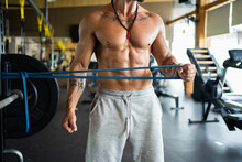 Cropped Unrecognizable Sportsman With Naked Torso Exercising With Elastic Band While Pumping Arms During Workout In Fitness Center