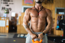 Cropped Unrecognizable Muscular Shirtless Male Athlete Standing With Heavy Kettlebells In Gym During Functional Workout And Looking Away