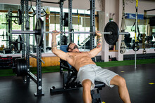 Powerful Male Athlete Doing Bench Press Exercise With Heavy Barbell While Training In Contemporary Gym