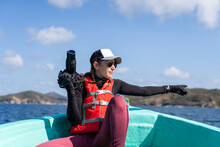 Cheerful Female Tourist With Digital Photo Camera Sitting On Boat During Trip On Wavy Ocean Under Cloudy Blue Sky