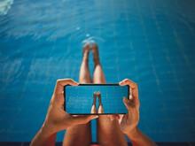 From Above Of Crop Anonymous Barefoot Female Taking Photo Of Legs On Cellphone Over Swimming Pool With Pure Water