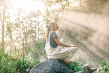 Side View Of Young Woman Sitting On Stone Near Calm Lake And Magnificent Waterfall On Sunny Day