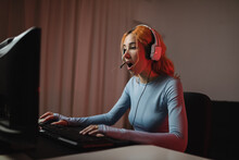 Side View Of Delighted Female Gamer In Headphones Playing Videogame While Sitting At Table At Home