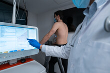 Crop Medic Analyzing Data On Digital Monitor During Cardiac Stress Test Of Male Patient Walking On Treadmill