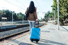 Back View Of Anonymous Female Traveler With Suitcase Walking Along Platform At Railway Station On Sunny Day