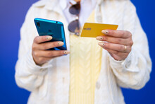 Cropped Unrecognizable Stylish African American Female Paying With Plastic Card During Online Shopping Via Mobile Phone While Standing On Blue Background In Studio