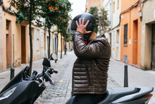 Side View Of Unrecognizable Masculine Male Motorcyclist With Helmet On Motorbike In Town