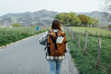 Back View Of Anonymous Female Hiker With Route Map In Rucksack Strolling On Countryside Roadway Against Mount