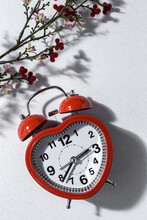 Top View Of Red Alarm Clock In Shape Of Heart And Bunch Of Fresh Lavender Flowers In Vase Arranged On White Background In Studio