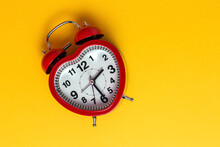 Red Metal Alarm Clock In Shape Of Heart Placed On Vibrant Yellow Background In Studio