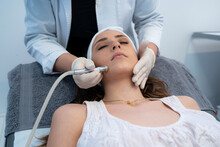 Cropped Unrecognizable Professional Cosmetologist Using Special Equipment And Doing Microdermabrasion Facial Treatment For Female Client In Modern Beauty Clinic