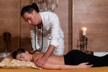 Male Spiritual Therapist Massaging Arm Of Topless Female With Closed Eyes Lying On Cushion Indoors