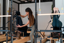Flexible Female Stretching Legs With Help Of Personal Instructor While Doing Exercises On Pilates Reformer
