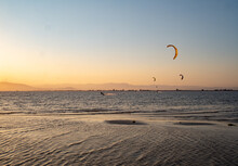 Distant Unrecognizable Adventurers Paragliding Over Calm Rippled Sea Water Against Sunset Sky In Summer Evening